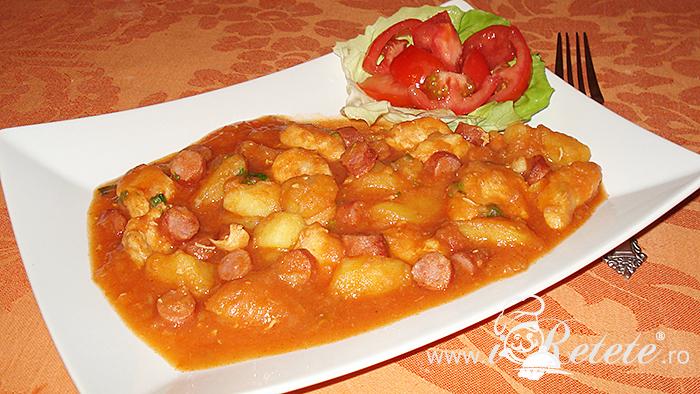 Tocanita de cartofi cu pui si carnaciori servita cu rosii proaspete